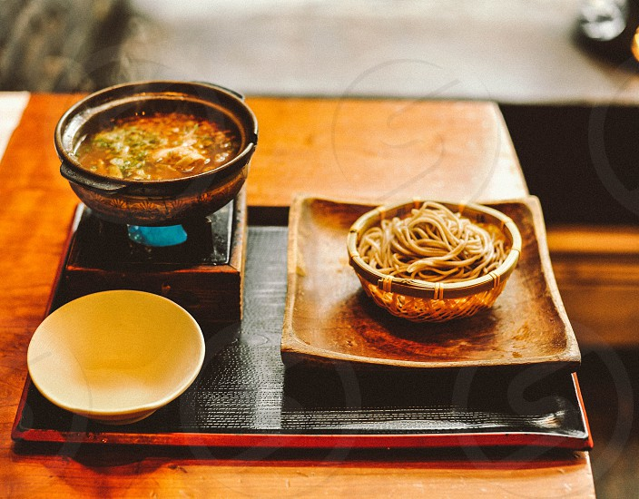 pasta in bowl beside soup near white ceramic bowl photo