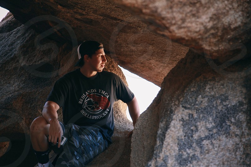 man in black crew neck t-shirt and blue shorts sitting on brown rock photo