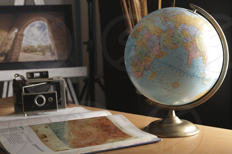 globe in studio background architectural photography an old camera and a book of world geography photo
