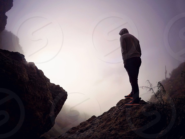 Man boy hiking mountain rocks cloudy Arizona  photo