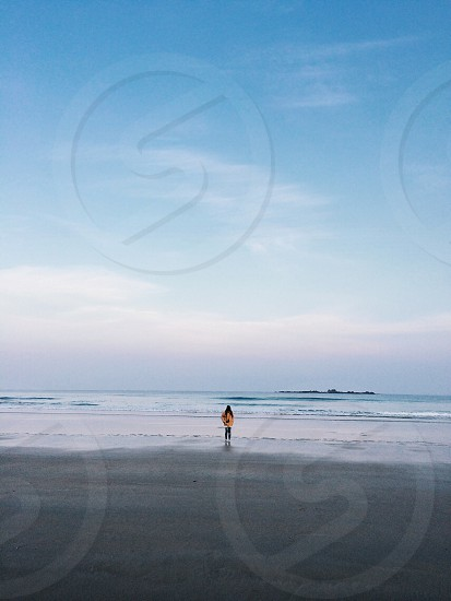 woman wearing white long sleeved shirt standing on sea shore photo