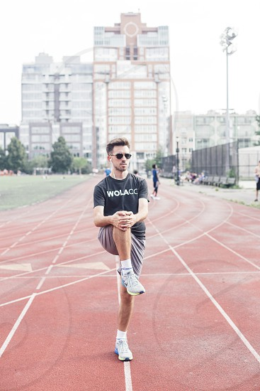 Male runner stretching track and field running track.  photo