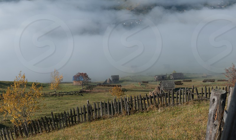 Barns on the hill in the fog photo