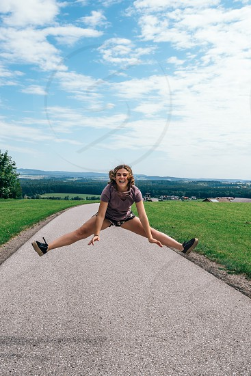 Happy young woman jumping on a road photo