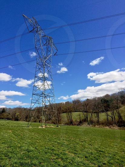 gray metal electrical tower on green grass field photo