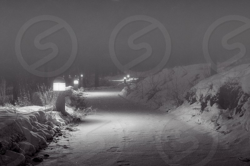 asphalt road covered by snow with post lamp beside during night photo