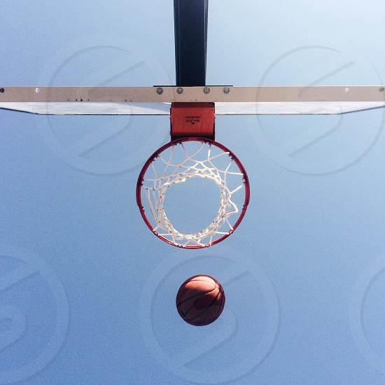 white black and red basketball ring and ball low angled photography photo