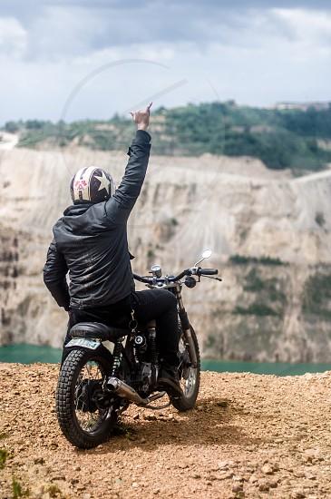 man wearing black leather jacket and white black full face helmet riding black motorcycle near lagoon photo