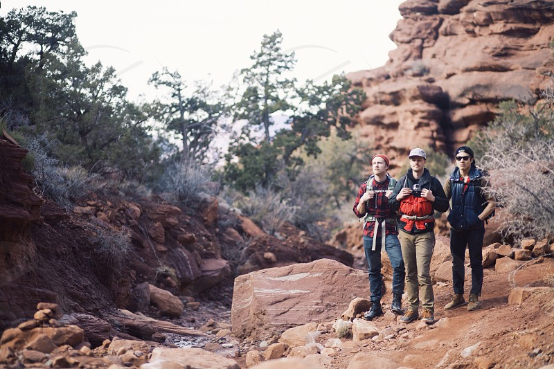 three persons standing on rock formation during day time photo