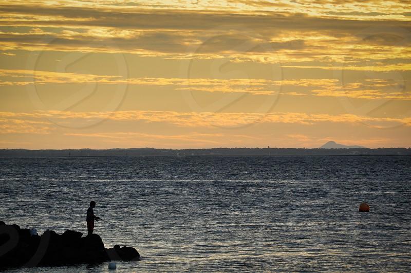 man standing on rock near the ocean photo