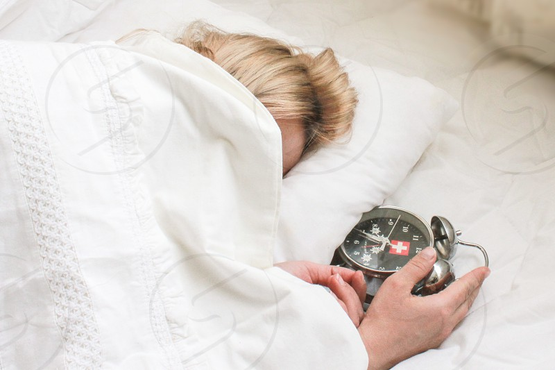 Woman sleeping in white sheets with alarm clock in her hand photo
