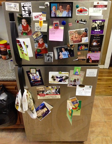 stainless steel refrigerator with photos and magnets photo