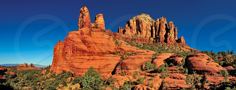 Two massive buttes of red sandstone along Chapel Trail in Sedona Arizona. Cathedral Rock can be seen on the left in the distance. photo