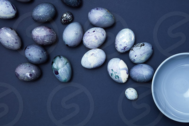 Many eggs of navy blue and white colors over navy blue background. Composition of eggs neat plate. Easter concept. photo