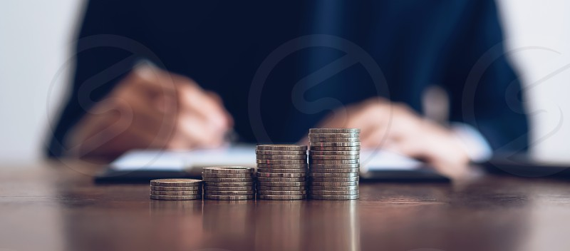 Coin to stack money financial Business Growth. Men background is signing documents. photo