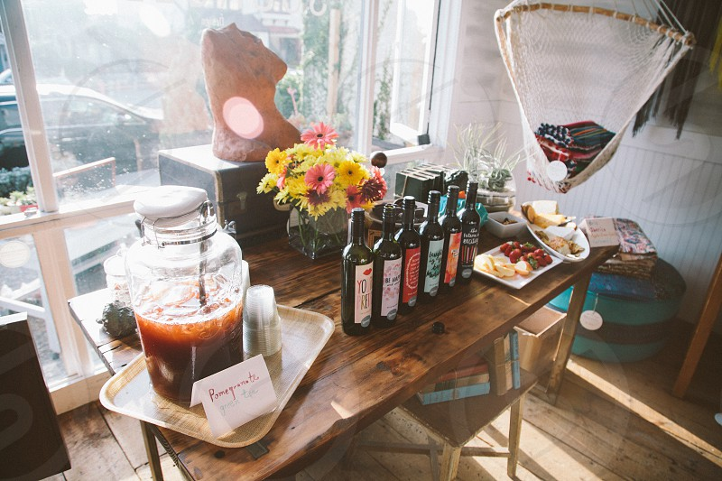 clear glass jar beside wine bottles on table photo