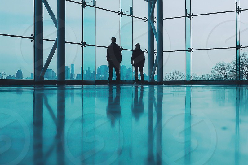 men standing on building window silhouette photo photo