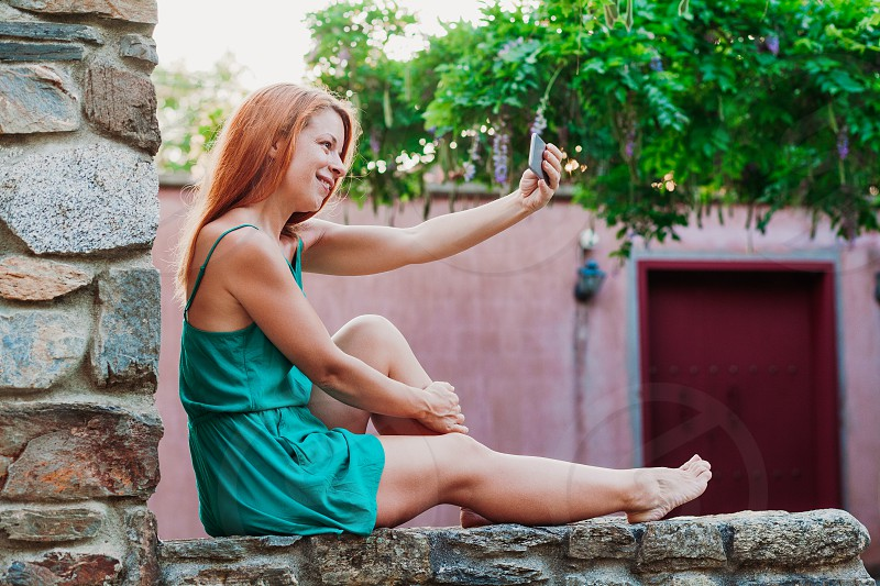 Young tourist woman taking a selfie in a Greek village photo