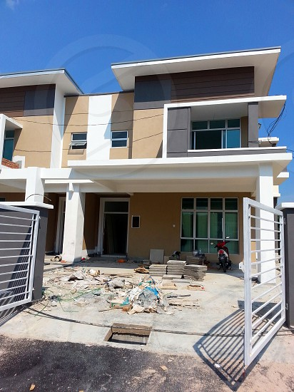 white and brown concrete house with gray metal gate on construction photo