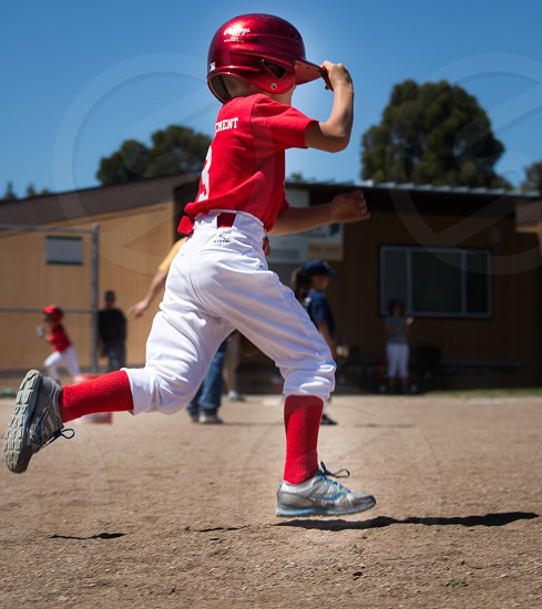 Baseball youth running from first to second base photo