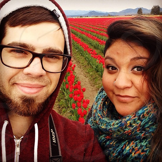bed of tulip flowers behind man in red and white zip-up drawstring hoodie beside woman in blue and multicolored crochet infinity scarf photo