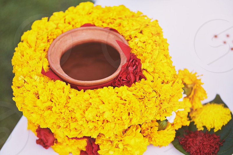 The clay pot cover with yellow garland The prayer and worship items for thread ceremony pooja (Puja) of the Indian wedding before wedding ritual. Focusing on the center of clay pot photo