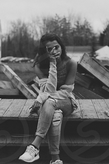 grayscale photo of woman sitting on a dock photo
