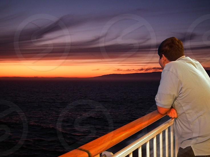 man leading on ship deck railing photo