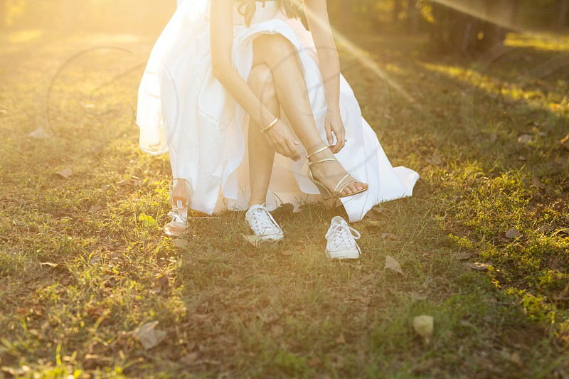 Bride changes into tennis shoes in the golden sunlight photo