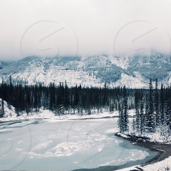 snow covered wooded area at base of mountain by frozen lake photo