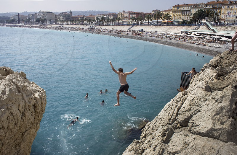 YoungmanjumpingoceanNicebeachSouthernFranceFranceEuropeSummerVacation photo