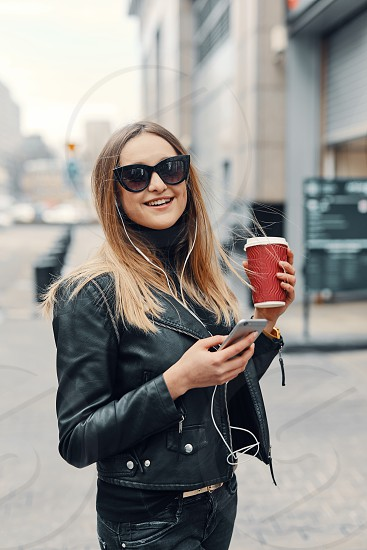 Pretty girl stand on the street listen music from her headphones and drink coffee windy weather photo