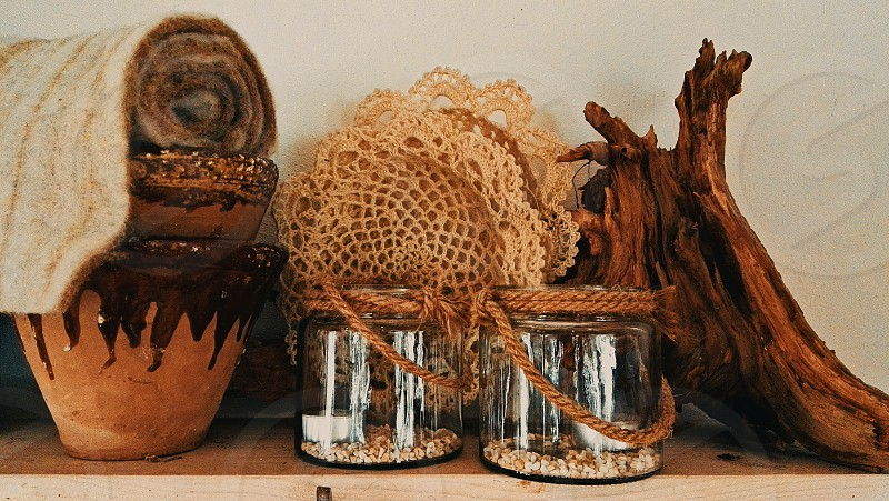 a wooden shelf with handmade clay pots wool lace a piece of bough and jar candlestick photo