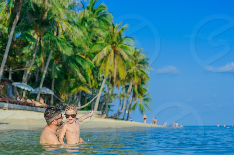 Family portrait: father and son sitting in the water on a tropical beach. Cute little boy points a finger into the distance photo