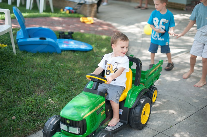 boy riding green black and yellow tractor toy photo