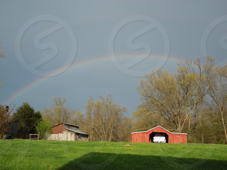After a rain storm a rainbow pops out over the farm photo