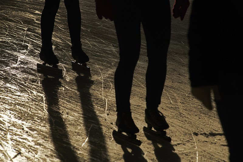 Beautiful silhouettes of people ice skating in winter sunshine with long shadows and motion blur photo