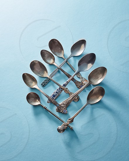 Pattern made of metal vintage spoons on a blue paper background top view photo