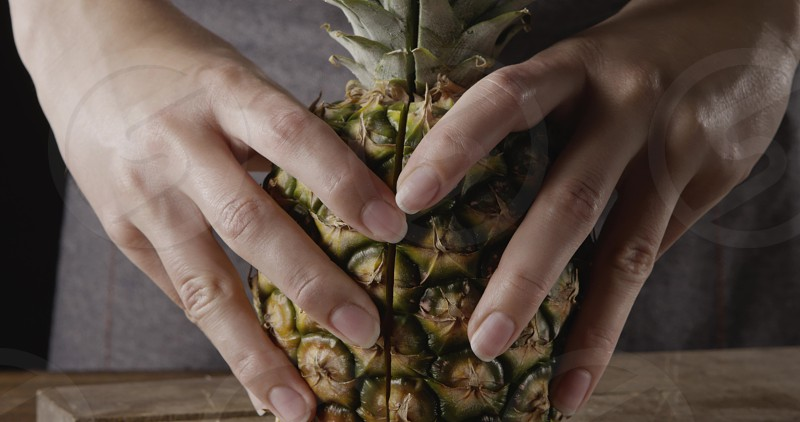 Woman's hand show two halves of fresh ripe natural organic juicy tropical fruit pinapple on acutting board on a wooden background. Motion 4K UHD video 3840 2160p. Concept of vegetarian diet eating. photo
