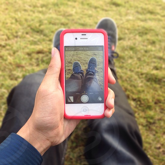 person holding a white iphone 4 taking a picture of his shoes photo