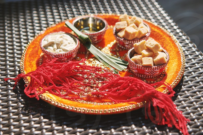 The prayer and worship items for thread ceremony pooja (Puja) of the Indian wedding before wedding ritual. Focus on the red thread and barfi dessert photo