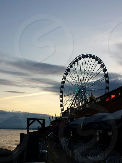 black parasol on sidewalk cafe in front of ocean overlooking ferry wheel during twilight photo