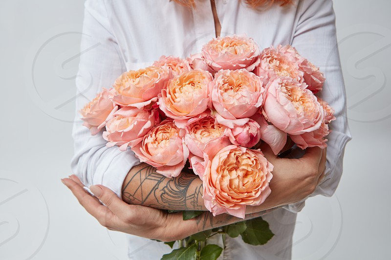 a bouquet of pink roses a woman with a tattoo is holding in her hands. The valentine's day photo