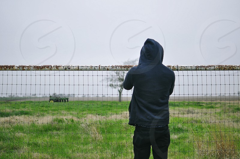 person in black jacket standing beside gray mesh fence under white clouds and blue sky photo
