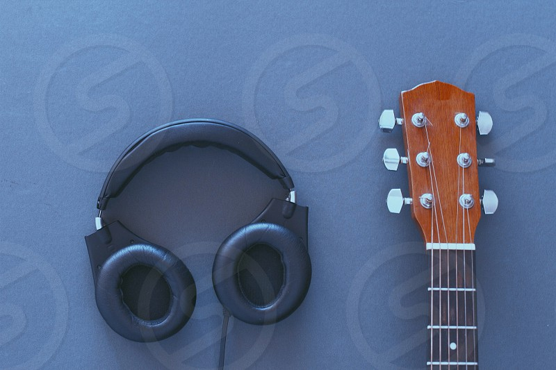 guitar neck and headphones laying next to each other photo