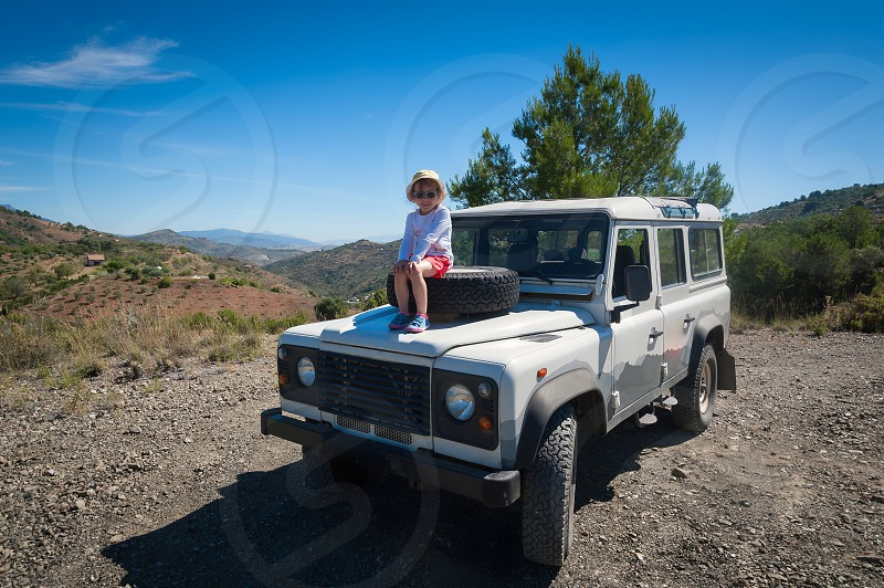 Rural Andalucia. Spain. Europe. Little girl admiring the view while sitting on front spare tyre on a bonnet hood in 4x4 terrain vehicle. photo