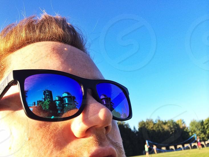 man wearing black wayfarer sunglasses staring at the sky photo