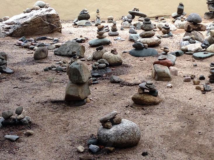 balancing rocks on flat brown surface photo