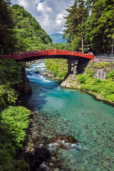 A red bridge spans over a crystal clear stream in Japan  photo