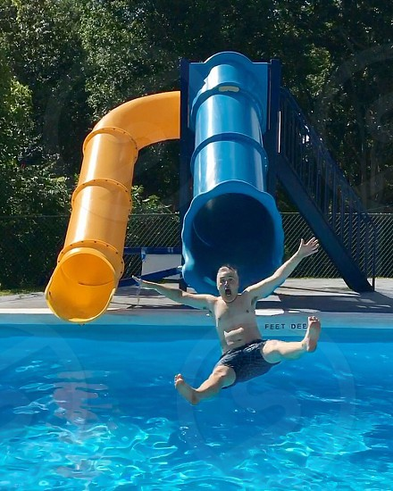 Man sliding into pool photo